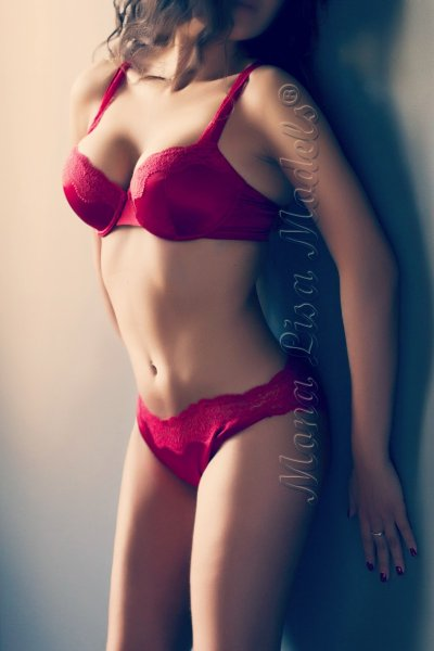 Alana posing in red lingerie touching the wall