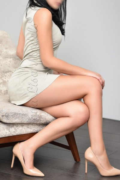 Naomi in a dress sitting on a plush chair